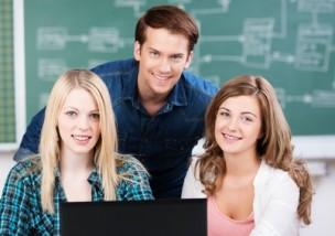 drei schüler mit laptop im klassenzimmer